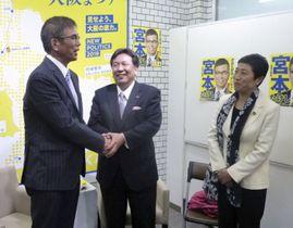 宮本岳志氏(左)を激励に訪れ、握手する立憲民主党の枝野代表。右は辻元国対委員長=15日夜、大阪府寝屋川市
