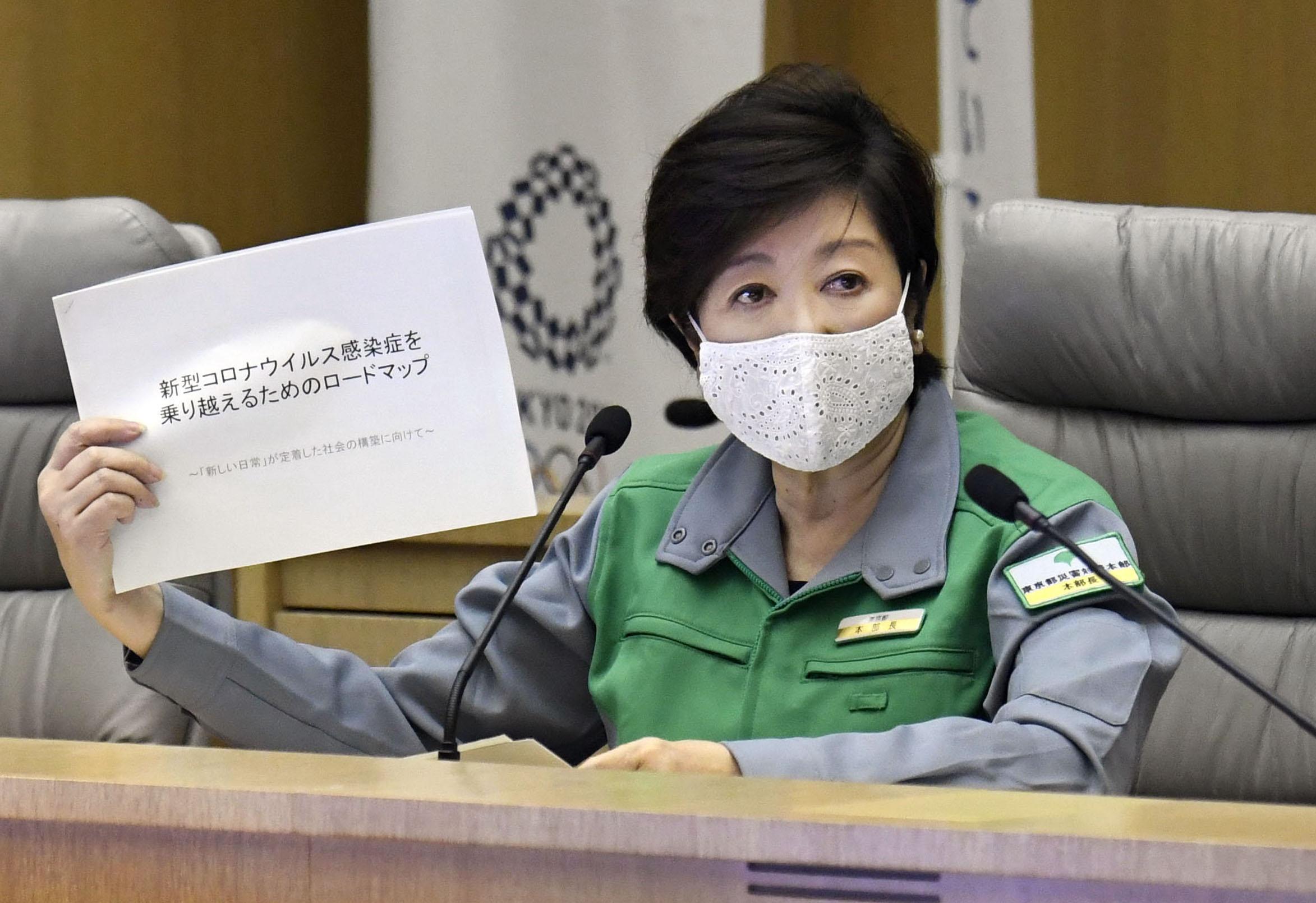 東京都の新型コロナウイルス対策本部会議で資料を手に発言する小池百合子知事=25日午後、東京都庁