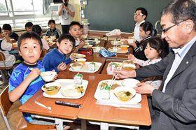 地元産の豚肉などを使った給食を味わう舞戸小児童と平田町長(右)
