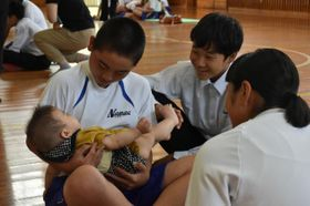 体験授業で乳児をあやす南郷中の生徒たち