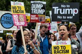 12日、トランプ米大統領が宿泊するロンドン中心部の米大使公邸周辺でデモ行進する人々(ゲッティ=共同)