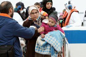 警備艇に救助され、船から下りる難民の女性ら=4月、ギリシャ東部レスボス島(共同)