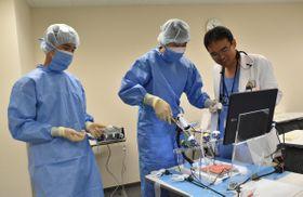 模擬骨に電動ドリルで穴を開けてプレートを固定する整形外科の手技に挑戦した生徒たち=同市松原の県立白鳥病院