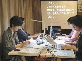 会話の内容をスクリーンに表示する要約筆記者ら=12日、札幌市