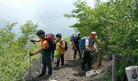 登山道沿いにロープを張る参加者