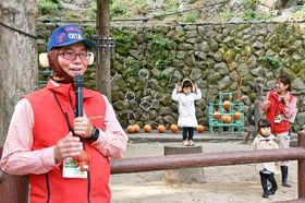 サルがいない高崎山の寄せ場で、サルに扮してガイドする園職員やボスが座る切り株の上でポーズを取る子ども