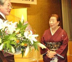 全国商工会議所女性会連合会から特別功労者表彰を受け、祝賀会で花束を贈られる小野山さん(右)=2007年1月