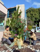 正門前で門松を飾り付ける職員