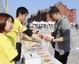 横浜赤レンガ倉庫で始まった「宇都宮餃子祭り」でギョーザを購入する来場者=20日午後、横浜市中区