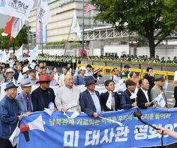 「南北共同宣言」の履行を訴え米大使館前を行進する人たち=15日、ソウル(共同)