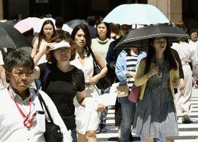 東京・銀座で強い日差しの中を歩く人たち=24日午後