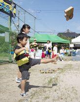 「ゲゲゲの鬼太郎ゲタ飛ばし大会」でげたを飛ばす子ども=25日午後、鳥取県境港市