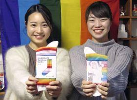 「レインボーはこだてプロジェクト」が販売する虹色の靴下を見せる田中美怜さん(左)と遠藤遥奈さん=北海道函館市