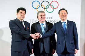 20日、IOC本部で開かれた平昌冬季五輪の北朝鮮参加を巡る4者会談で、バッハ会長を挟み握手を交わす金日国・北朝鮮オリンピック委員会委員長(左)、韓国の都鍾煥・文化体育観光相=ローザンヌ(ゲッティ=共同)