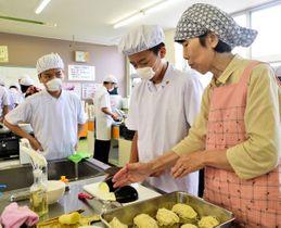 地元住民からアドバイスを受けながら三豊ナスを調理する生徒=香川県三豊市財田町、和光中