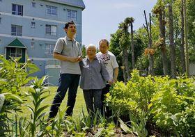 川瀬米子さん(中央)とニガイ・レフさん(右)夫婦の札幌市の住まいを訪れた後藤悠樹さん。「花が大好き。サハリンを思い出しながら植物を育てている」と部屋の前の家庭菜園で川瀬さんは話す=6月9日(撮影・堀誠)