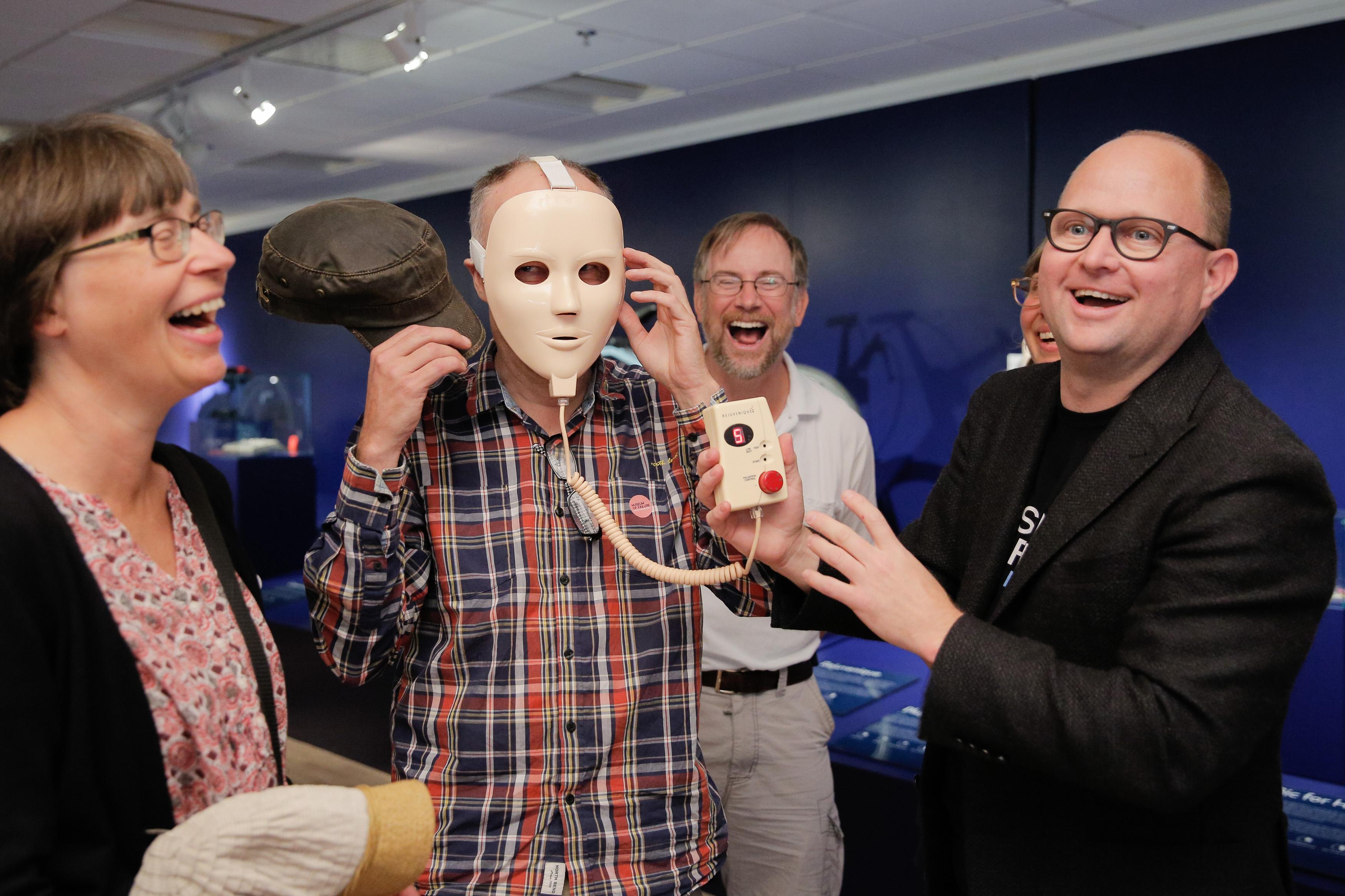 「顔面若返りマスク」を訪問客に試着させる失敗博物館のサムエル・ウエスト館長(右端)。電気が流れた瞬間、マスクを着けた人が声を上げ、周りは大笑い=スウェーデン・ヘルシンボリ(撮影・澤田博之、共同)(