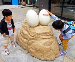 ティラノサウルスの卵のフィギュアを興味深そうに眺める子どもたち(長浜市元浜町・海洋堂フィギュアミュージアム黒壁龍遊館)