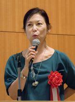 シンポジウムで講演する「NPOヒューマニティ」の小早川明子理事長=21日午後、東京都世田谷区