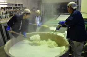 蒸し上がった酒米の湯気が立ちこめる中、新酒の仕込み作業を行う蔵人たち