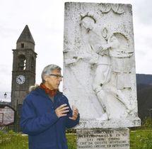 イタリア北部モンテレッジォの広場に立つ「本の行商人」の彫刻について説明をするジャコモさん(共同)