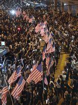 米議会による「香港人権・民主主義法案」の早期可決を求める集会で、会場周辺の道路を埋める大勢の市民と米国旗=14日、香港(共同)