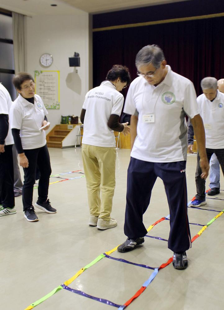 はしご状の運動器具をまたぐ認知症予防トレーニング(愛知県大府市の大府公民館)