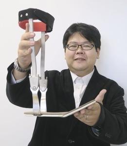 開発した装具を持つ井上淳さん