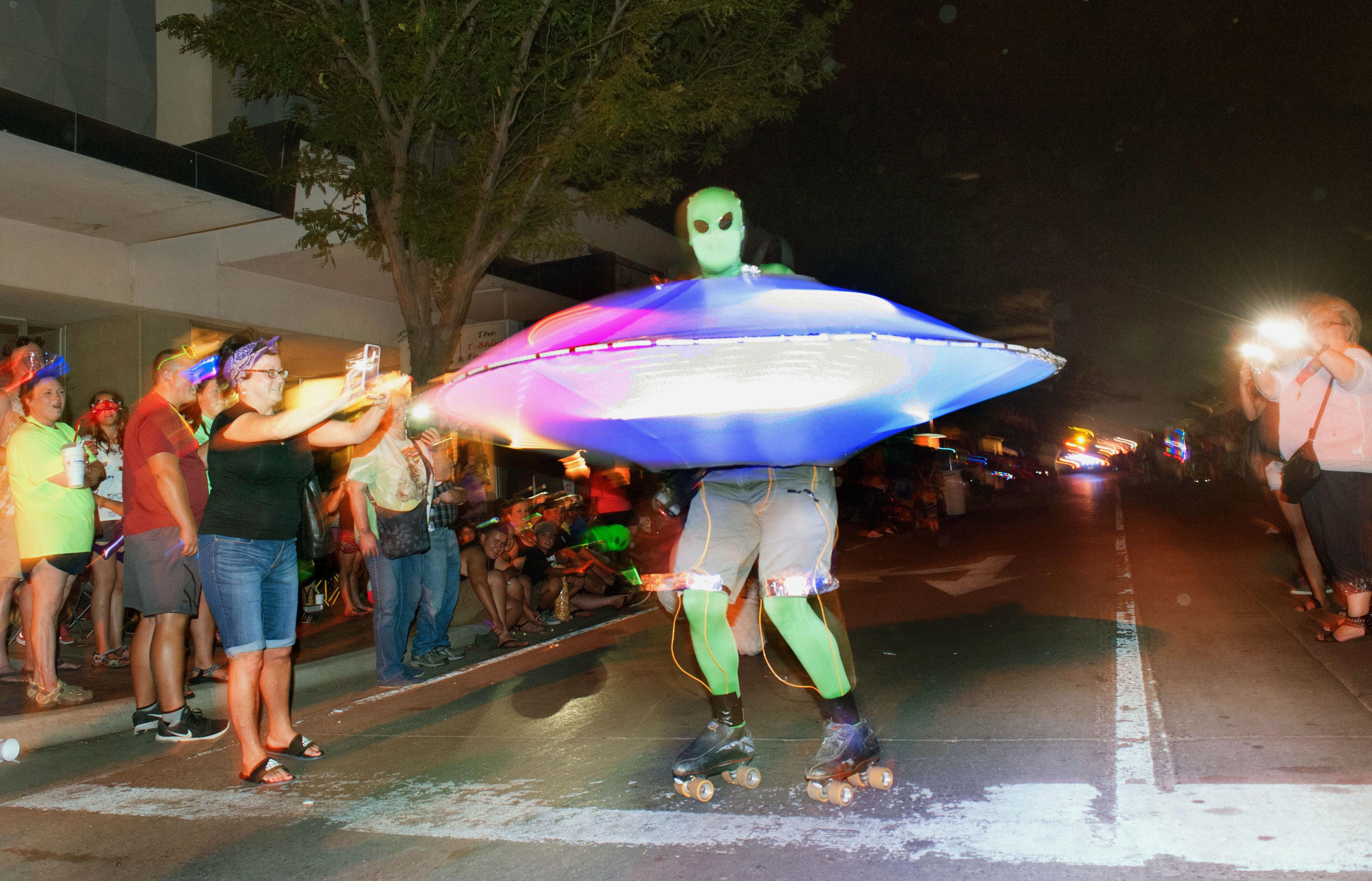 照明を落とした、フェスティバル恒例の夜のパレード。暗闇から宇宙人が次々に現れ、ローラースケートのUFO男にとりわけ大きな歓声が上がった=米ニューメキシコ州ロズウェル(撮影・鍋島明子、共同)