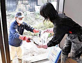 娘の手を借りて、浸水した家の片付けをする男性(左)=17日午後3時45分ごろ、いわき市