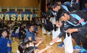 餅まきで市民と交流する川崎の選手