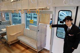 スマートドアの開閉ボタンを押す乗務員。優先席付近のつり手だけ色が違う=長崎市尾上町、JR長崎駅