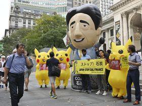 安倍首相に模したバルーンと石炭火力発電に抗議する人ら=23日、ニューヨーク公共図書館前(共同)