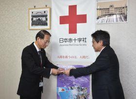 義援金の目録を受け取る日赤県支部の柳田俊治事務局長(左)=13日午前、宮崎市