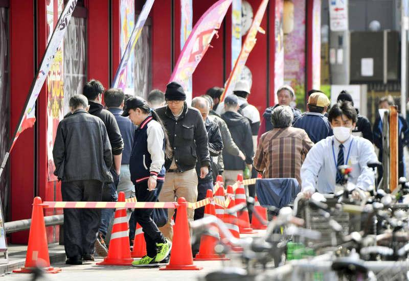 開店前のパチンコ店に並ぶ人たち=8日午前10時、大阪市西成区