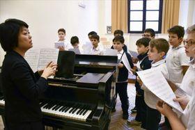 システィーナ礼拝堂合唱団の付属学校で授業をする富永正子さん(左端)=4月(共同)