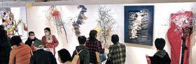 壁面を生かしたレリーフ作を鑑賞する来場者=金沢市のめいてつ・エムザ8階催事場