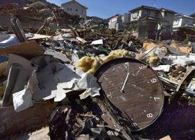 広島県熊野町の土砂崩れ現場に残る壊れた時計=15日午前8時14分