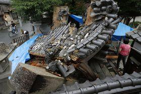 地震で倒壊した妙徳寺の山門。一部にブルーシートが掛けられていた=19日午後、大阪府茨木市