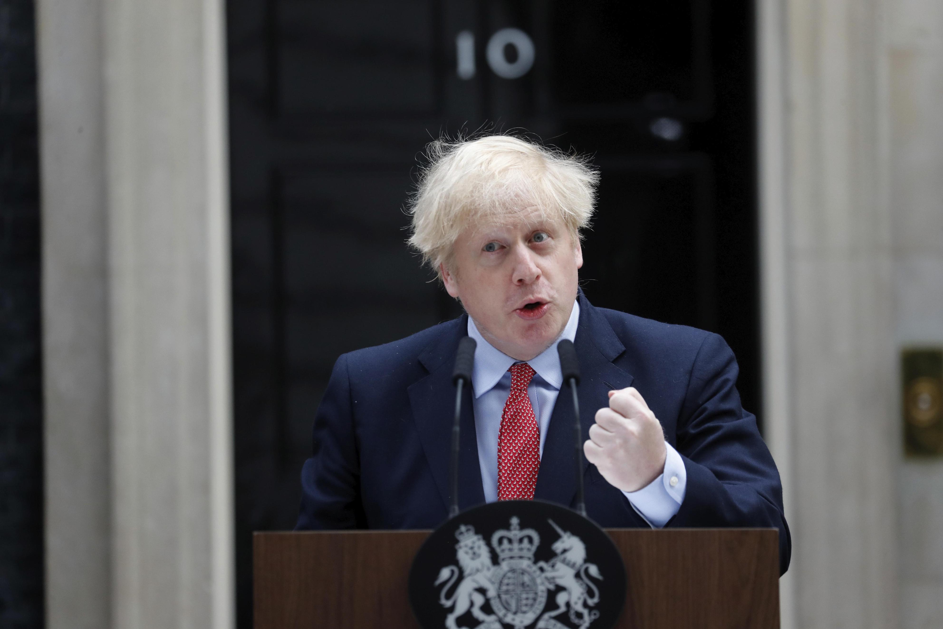 英首相官邸前で声明を読み上げるジョンソン首相=27日、ロンドン(AP=共同)