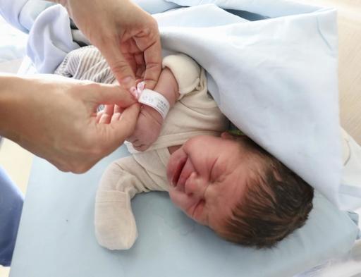 エストニア・タリンの病院で、11桁の個人識別番号が記されたバンドを巻き付けられる生まれたばかりの赤ちゃん=2019年9月(共同)