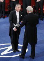 ノーベル賞授賞式で、スウェーデンのカール16世グスタフ国王(手前)から文学賞のメダルと賞状を受け取るカズオ・イシグロ氏=10日、ストックホルム(共同)