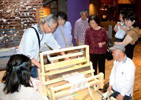 昔ながらの機織り機の作業を見学する家族連れら=観音寺市豊浜町、豊浜郷土資料館