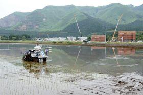 復旧した水田で3年ぶりの田植え作業にいそしむ日田政次さん。奥では国道57号北側復旧ルートの工事が進む=14日、阿蘇市