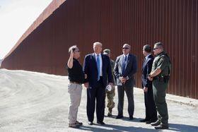 米西部カリフォルニア州のメキシコとの国境地帯で、「壁」建設を視察するトランプ大統領(左から2人目)=18日(ロイター=共同)