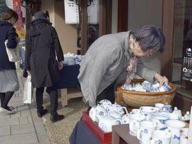 開幕した「秋の有田陶磁器まつり」で陶磁器の品定めをする人ら=21日午前、佐賀県有田町