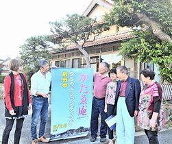 ゲストハウスとなる民宿の前で、地域住民と構想を語り合う青戸裕司さん(左から2人目)=松江市美保関町片江