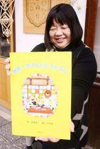 絵本「世界一やさしいレストラン」を手にする綾部さん