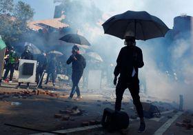 ガスマスクと傘を身に着け、れんがが散らばる路上で警察と衝突するデモ隊=17日、香港(ロイター=共同)