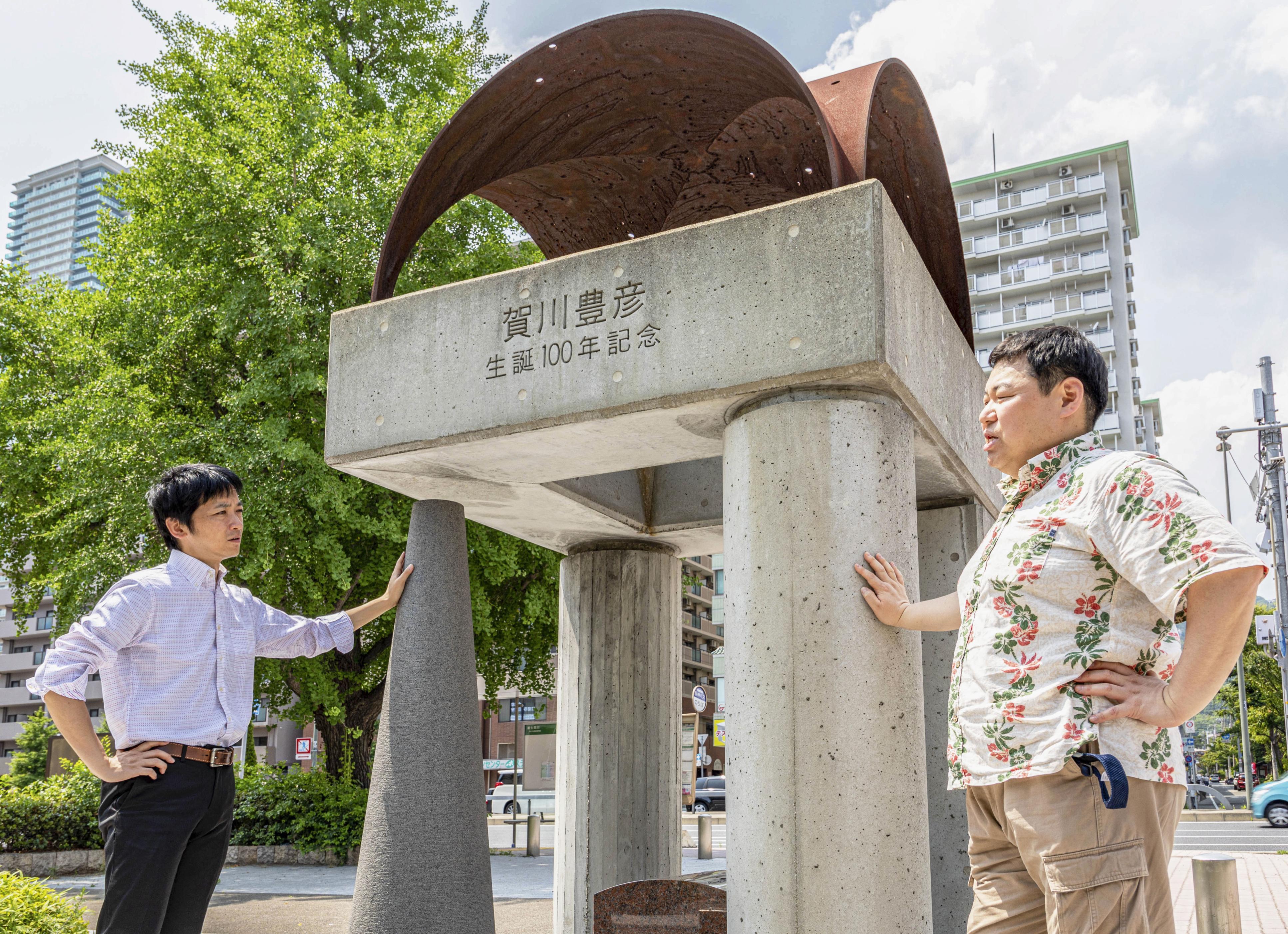 賀川豊彦はこの地で貧しい人々の救済に打ち込んだ。生誕100年の記念碑前で語り合う松谷信司(左)と波勢邦生=神戸市
